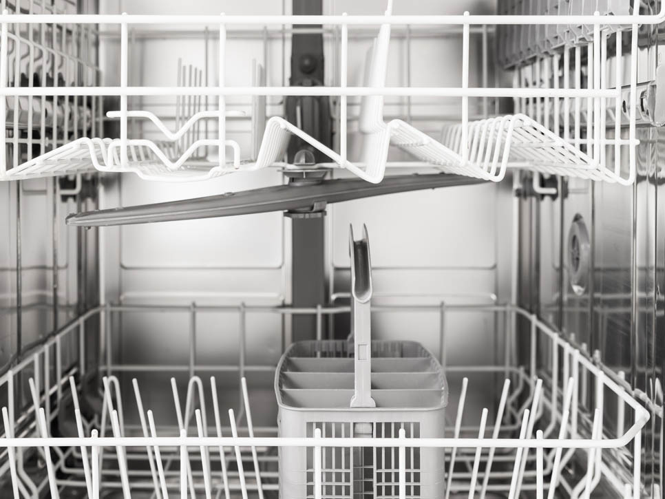 A black and white photo of the inside of a clean dishwasher without mold, food, or dirty dishes.